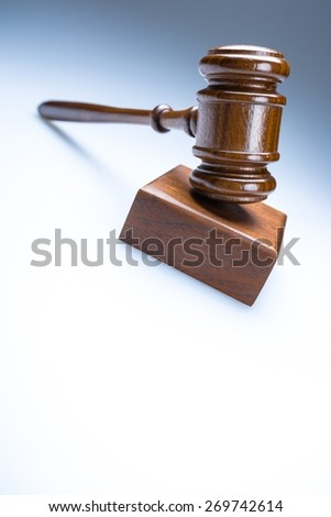 Gavel. A wooden judge gavel and soundboard on blue  background in perspective - stock photo