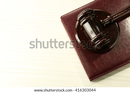 Gavel and book on light wooden background