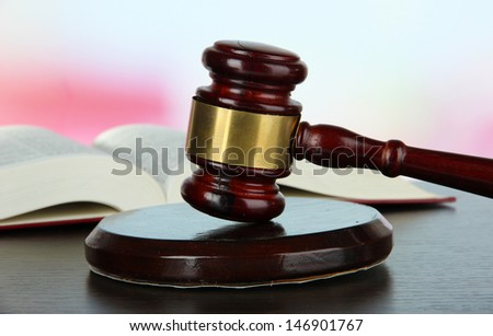 Gavel and book on table on light background