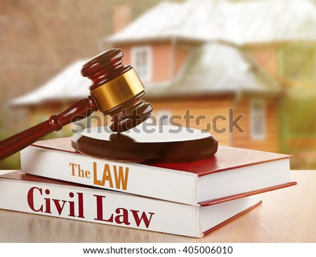 Gavel and books on wooden table on building background. Auction concept - stock photo