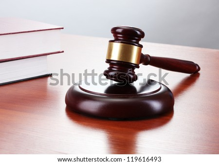 gavel and books on wooden table on gray background