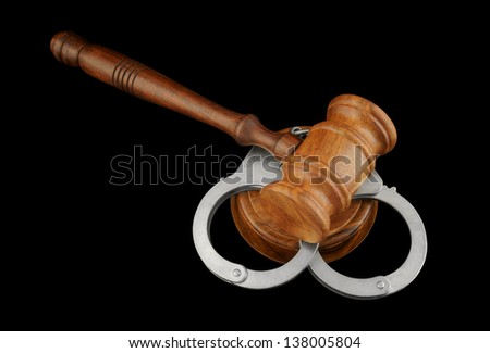 Gavel and handcuffs isolated on black - stock photo