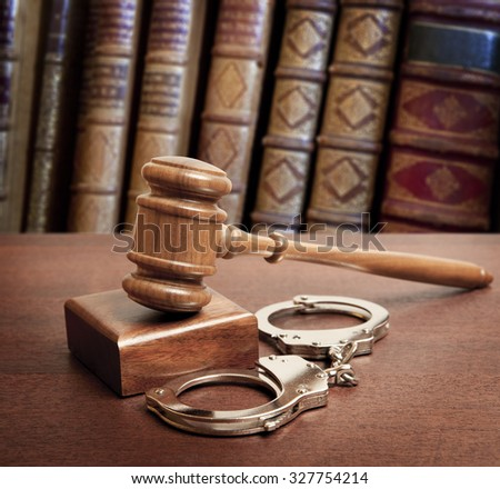Gavel and handcuffs on book background - stock photo