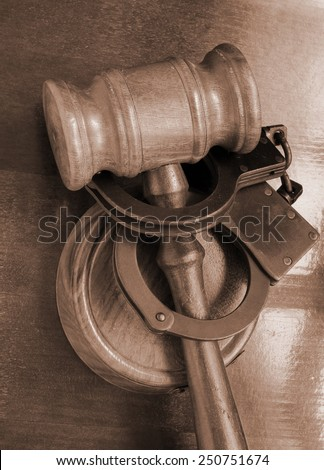 Gavel and handcuffs on table - stock photo