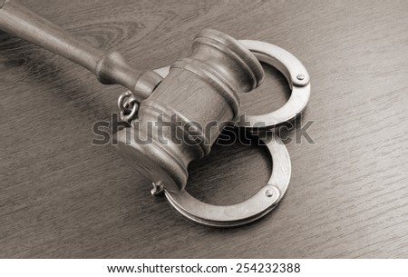 Gavel and handcuffs on wooden table background  - stock photo