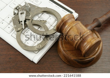 Gavel and handcuffs with computer keyboard on table - stock photo