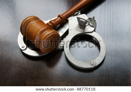 Gavel and handcuffs with keys on wooden background - stock photo