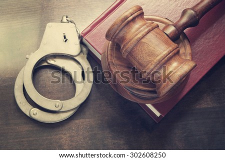 Gavel and handcuffs with red legal book on wooden table - stock photo