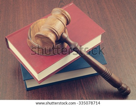 Gavel and legal books on wooden table, legal concept - stock photo
