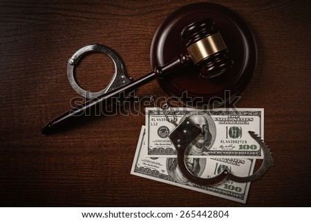 Gavel and money on wooden table - stock photo