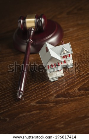 Gavel and Small Model House on Wooden Table. - stock photo