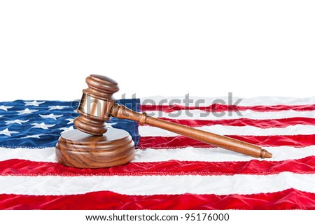Gavel and sound block on an American flag with a white background for placement of copy. - stock photo