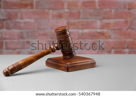 Gavel and sound block on brick wall background