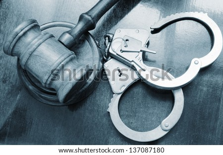 Gavel and steel handcuffs on wooden background - stock photo
