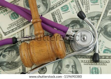 Gavel and stethoscope on dollars background - stock photo