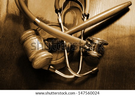 Gavel and stethoscope on wooden background - stock photo
