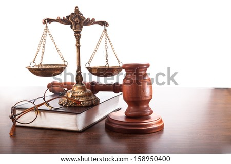 Gavel, antique bronze scales, glasses and a book on the table - stock photo