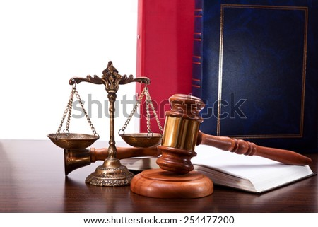 Gavel, bell, bronze scales, a book and a folders on the table walnut - stock photo