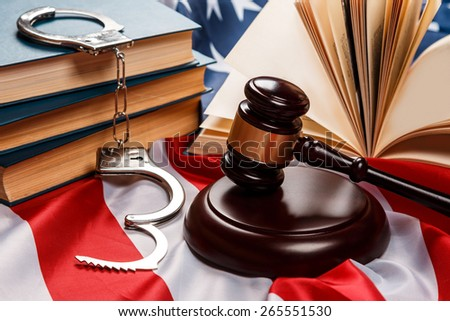 Gavel, books and handcuffs over american flag - stock photo