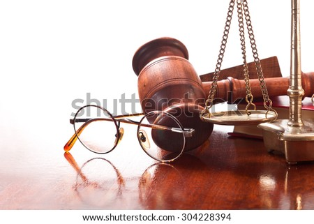 Gavel, bronze vintage scales, book and glasses in a round frame on a table - stock photo