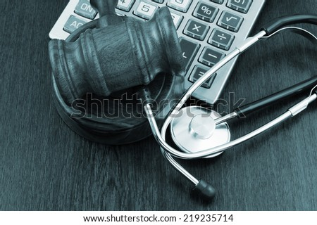 Gavel, calculator and stethoscope on wooden table - stock photo