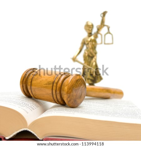 gavel close up on a book of laws and justice statue on a white background
