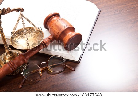 Gavel, glasses, book and scales on the table - stock photo