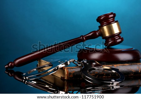Gavel, handcuffs and book on law on blue background - stock photo