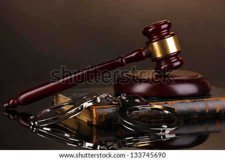 Gavel, handcuffs and book on law on brown background - stock photo
