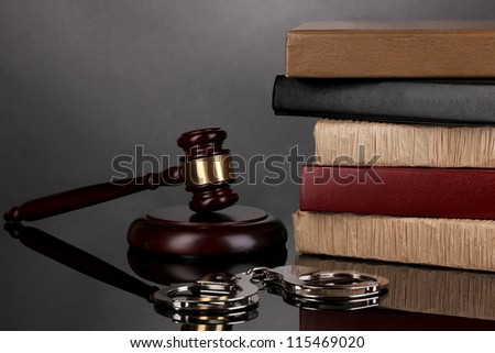 Gavel, handcuffs and books on law isolated on black