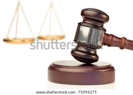Gavel in action and scale of justice on a white background - stock photo