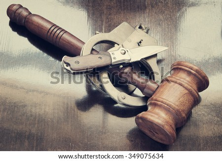 Gavel, knife and handcuffs on wooden background, criminal concept - stock photo