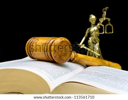 gavel, law book and the statue of justice on a black background