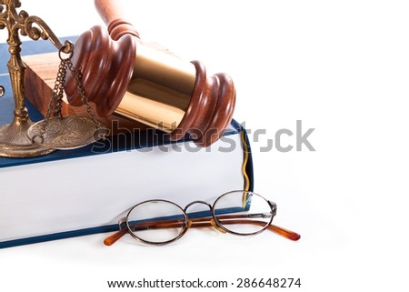 Gavel, old bronze scales, round glasses and a book on a white background