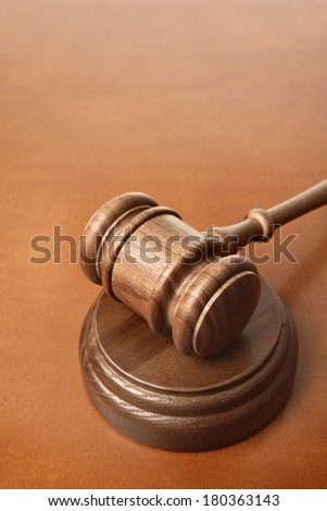 Gavel on brown leather surface