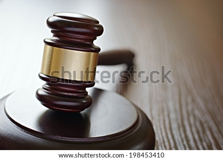 Gavel on sounding block on wooden surface