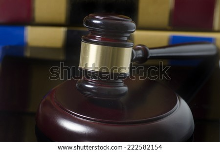 Gavel on wood block with legal books in background - stock photo
