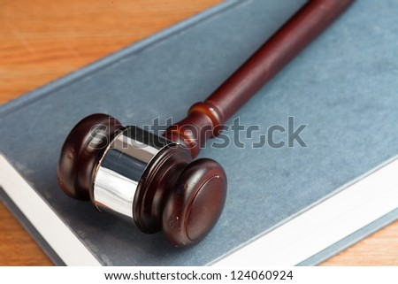 Gavel resting on a blue book on desk - stock photo