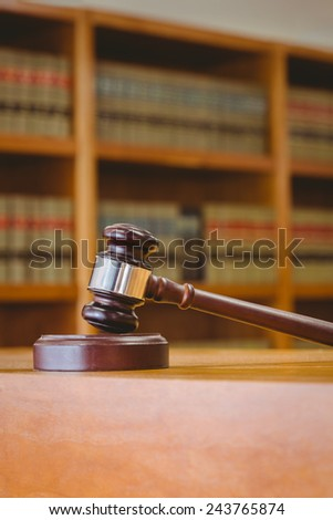 Gavel resting on sound block in library - stock photo