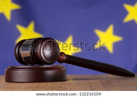 Gavel resting on sound block with european union flag in background - stock photo
