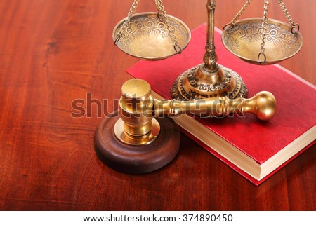 Gavel, vintage antique scales and book on a wooden table - stock photo