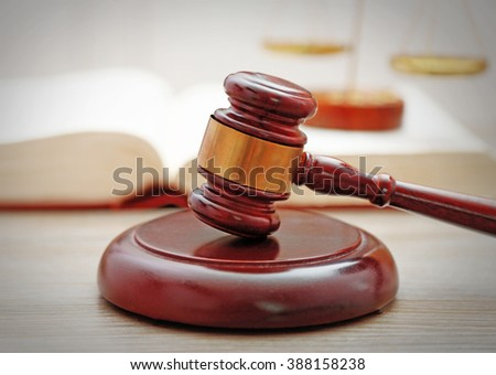 Gavel with justice scales and open book on wooden table, close up