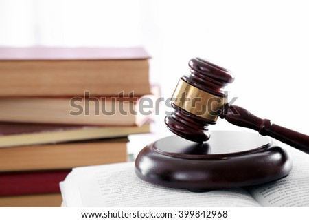 Gavel with pile of books on light blurred background