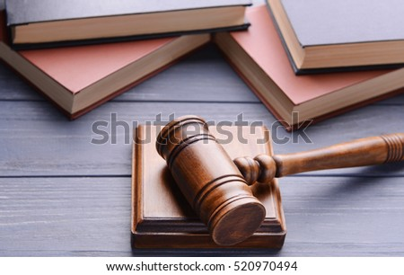 Gavel with sound block and books on wooden background, closeup