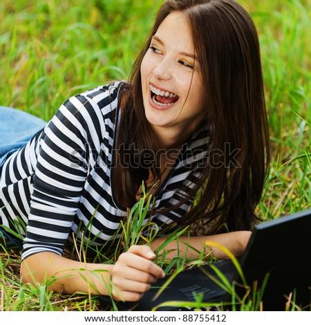 gay beautiful woman long hair lying grass meadow notebook - stock photo