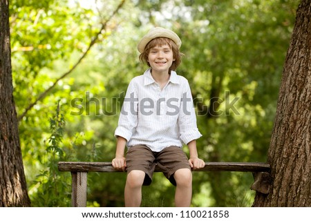 Gay boy in a hat and shirt sitting on bench - stock photo