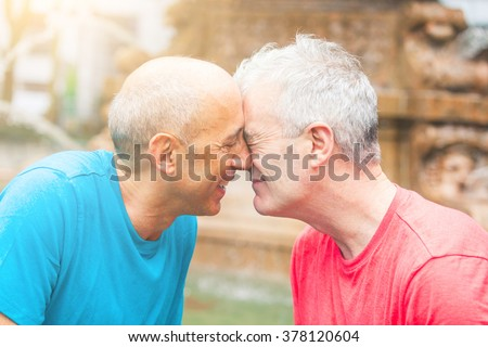 Gay couple at park in New York. They are two men in their early sixties, standing face to face, cuddling and smuggling. Homosexual love concept