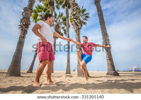 Gay couple dancing and having fun on the beach - Homosexual partners celebrating and having party outdoors - stock photo