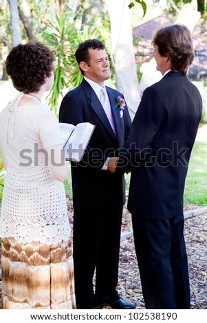 Gay couple saying their wedding vows in front of a young female minister.
