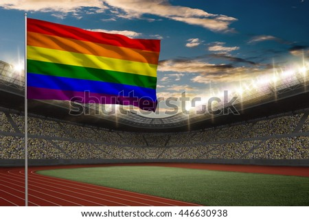 Gay Flag in front of a Track and field Stadium with fans.